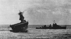 Guarded by a destroyer, the Yorktown lists dangerously to port.