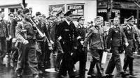 German prisoners of war marching through the streets of Gravenhurst, Ontario, on their way from the train station to the prisoner of war camp.