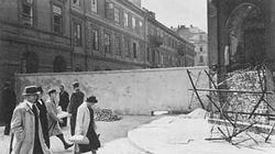 Polish civilians pass the wall of the Jewish ghetto in Warsaw.