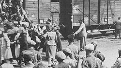 Loading Jewish deportees on cattle car from the Lodz ghetto. The men with military caps are Jewish police.