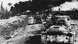 With smoke still pouring from a bombed out town, a unit of German Pzkpfw 38(t) tanks drives on into Russia.