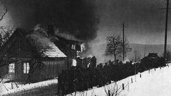 German infantry, led by a Panzer, pause by a burning village in Norway before resuming their advance in March 1940.