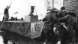 A wounded British commando is helped to a landing craft as victorious troops leave Vaagso with 100 German prisoners.