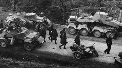 Greek prisoners of war march past German armoured cars.