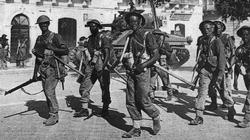 British troops walk through the streets of Pachino, Sicily.