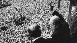 Winston Churchill greet an ecstatic crowd with his traditional two fingered Victory sign.