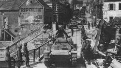 In a captured French town, a German Pzkpfw II grinds across an improvised bridge.